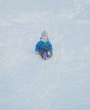 En el niño feliz de la colina en invierno Imagen de archivo