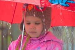 En el niño triste de la lluvia con un paraguas fotos de archivo