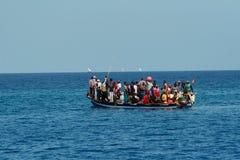 En el océano flota su barco con el grupo grande de africanos. Imagen de archivo