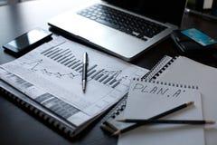 En el ordenador portátil de la tabla, cuaderno los graficks de las finanzas y planean a Foto de archivo
