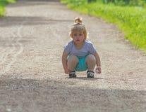 En el paseo, el niño se sienta en el camino Imagenes de archivo