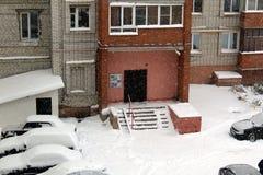 En el patio de un edificio alto todo se cubre con nieve después de una nevada fotos de archivo libres de regalías