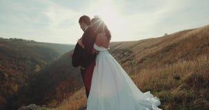 En el pico de la montaña con puesta del sol asombrosa la novia detiene a su novio 4K almacen de video