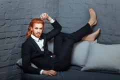 En el sofá con sus pies es el individuo de moda Fotografía de archivo libre de regalías