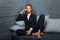 En el sofá sienta a piernas cruzadas al individuo Fotografía de archivo