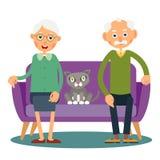 En el sofá siente la mujer, el hombre y el gato mayores Foto de archivo libre de regalías