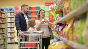 En el supermercado: Familia feliz de tres, llevando a cabo las manos, paseos a trav?s de la secci?n del reci?n hecho de la tienda almacen de metraje de vídeo