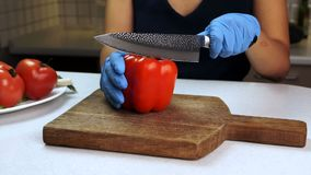 En el tablero de madera las manos femeninas en los guantes de goma cortaron l pimienta dulce roja metrajes