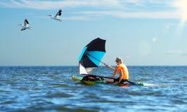 En el tablero de paleta, la cogida del viento con un paraguas flota a Imagen de archivo libre de regalías