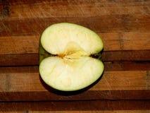 En el tablero se corta en manzana a medias verde Fotografía de archivo libre de regalías