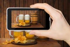 En el teléfono los vidrios con la cerveza y los microprocesadores Foto de archivo