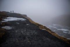 En el top de la cascada islandesa en nieve y lluvia del invierno, el caminar de los turistas Imagen de archivo libre de regalías