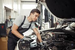 En el trabajo: un mecánico de coche está buscando insectos en un motor imagenes de archivo