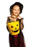 En el traje de la bruja que sostiene el cubo de Halloween Imagenes de archivo