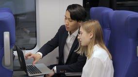 En el tren un hombre asiático muestra a vidrios que llevan de una mujer un ordenador portátil almacen de metraje de vídeo