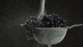 En el vídeo que vemos las uvas en un tamiz, en el centro del agua video comienza caída del top en un jet, cámara va almacen de video
