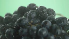En el vídeo vemos las uvas, en el medio del agua video comenzamos a verter del top, primer, fondo verde almacen de metraje de vídeo