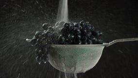 En el vídeo vemos las uvas en un tamiz, comienzo del chorro de agua nos caemos del top, fondo negro metrajes