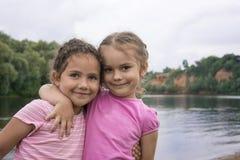 En el verano, dos amigos jovenes se colocan de abarcamiento en los vagos del río Fotos de archivo