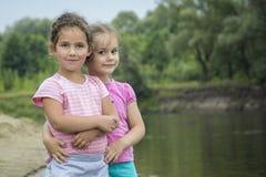 En el verano, dos amigos jovenes se colocan de abarcamiento en los vagos del río Imagen de archivo libre de regalías