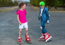 En el verano en el parque, un muchacho y una muchacha ruedan en pcteres de ruedas foto de archivo libre de regalías