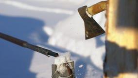 En el woodpile puesto un registro Leña en invierno Hacha que taja el registro metrajes
