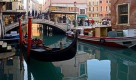 En elasticitet av en kanal i Venedig med fartyg och färgrika byggnader på en solig vinterdag royaltyfri foto
