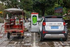 En elbil och populära trehjulingar åker lastbil sparkcykeln som laddar på gatan i den turist- staden Yangshuo av Kina royaltyfria foton