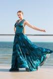 En elegant dam med den långa blonda hästsvansen och i en lång vinkande smaragdklänning som poserar nära ett blått hav Härlig flic Fotografering för Bildbyråer