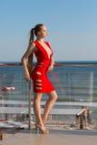 En elegant kvinna på en ljus havsbakgrund En härlig dam i en ljus röd klänning med en dekolletage royaltyfri bild