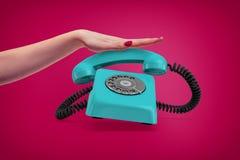 En elegant kvinnlig hand trycker på ner ett handtag av en retro blå roterande telefon som ringer och hoppar nästan upp arkivbild