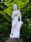 En elegant staty av en kvinna som göras av murbruk Stå på en sockel bland de gröna busksnåren av träd royaltyfria foton