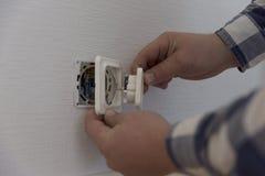 En elektriker installerar kontakten prövkopior för målarfärgrulle Royaltyfri Bild