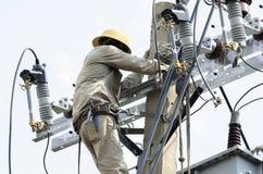 En elektriker som reparerar tråd på elkraftpol Arkivfoton