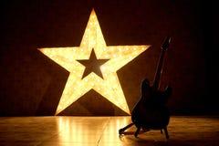 En elektrisk gitarr på bakgrunden av en stor elektrisk stjärna Arkivfoton