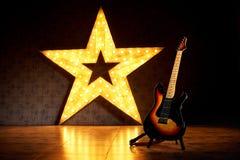 En elektrisk gitarr på bakgrunden av en stor elektrisk stjärna Arkivfoto