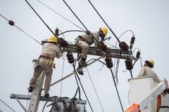 En elektrisk linjearbetare som arbetar på en linje Arkivfoto