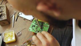 En elektroniktekniker löder ett elektriskt bräde med processorer Elektrisk utrustning f?r f?rlagereparationer ovanf?r sikt vid fö stock video