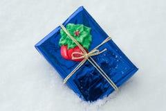 En emballerad gåva med julsymboler, vit snöbakgrund Royaltyfri Fotografi