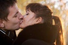 En embrassant des couples sur le fond de feuilles au soleil survivez Photo stock