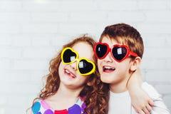 En embrassant le garçon et la fille avec le coeur de sunglassec formez DENT HEUREUSE Photographie stock libre de droits