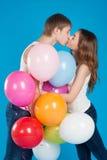 En embrassant le jeune amour couplez tenir beaucoup de ballons dans le studio Photographie stock libre de droits