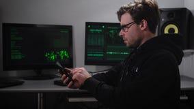 En en hacker i datasalen En man i solglasögon och med en smartphone förestående som försöker att hacka information från utländskt arkivfilmer