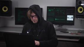 En en hacker i datasalen Mannen med exponeringsglas och bärbara datorn på en hand som försöker att hacka information från utländs lager videofilmer