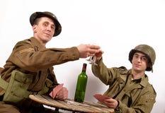 En engelsk soldat och en amerikansk soldat dricker ett exponeringsglas av vin Arkivbilder