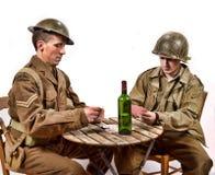 En engelsk soldat och en amerikansk soldat som spelar kort Royaltyfri Bild