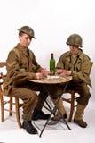 En engelsk soldat och en amerikansk soldat som spelar kort Arkivbild