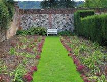 En engelsk tillbaka trädgård med bänk- och blommakorgen Royaltyfri Bild