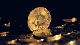 En enkel guld- bitcoin står bland många andra mynt arkivfilmer