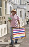 En enkel holidaymaker som bär en deckchair royaltyfria foton